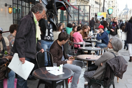 PARIS - MAY 4   Parisians and tourist enjoy eat and drinks in cafe sidewalk in Paris, France on May 4, 2013  Paris is one of the most populated metropolitan areas in Europe