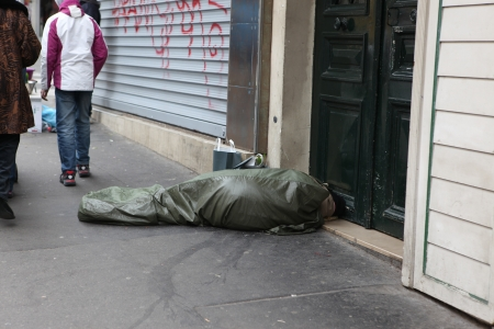 evicted: PARIS - MAY 1   Homeless man curled up under a plastic tarpaulin, asleep on the street, May 1, 2013 in Paris, France  Today, France has 130,000 homeless, and every day one of them dies Editorial