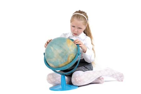 8 year old school girl with book and globe smiling on white background photo