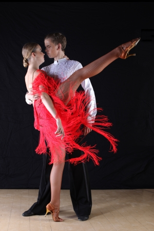 Latino dancers in ballroom against black background photo