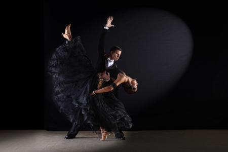 couple dancing: dancers in ballroom against black background