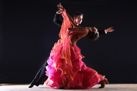 tango dance: Latino dancers in ballroom against black background