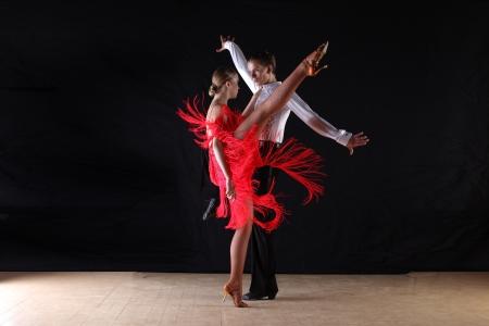 Latino dancers in ballroom against black background photo