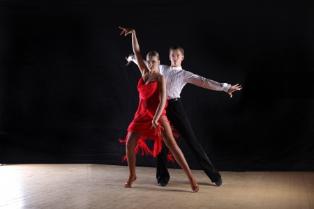 tango: Latino dancers in ballroom against black background