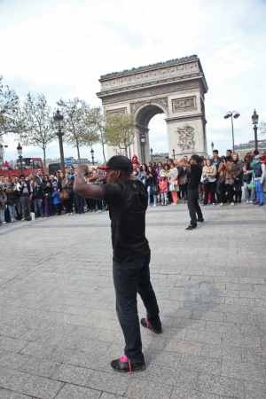 PARIS - APRIL 27: B-boy doing some breakdance moves in front a street crowd, at Arch of Triumph, April 27 2013, Paris, France
