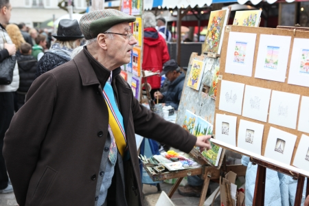 PARIS - CIRCA 1 MAY 2013: Public painter and buyer on Montmartre hill in Paris circa 1 May 2013 in Paris, France. Many artists worked around the community of Montmartre such as Pablo Picasso or Vincent van Gogh