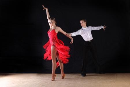 dancers in ballroom against black background