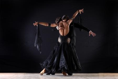 Latino dancers in ballroom against on black  Foto de archivo