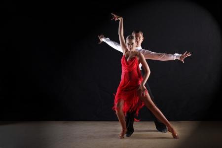 Latino dancers in ballroom against black