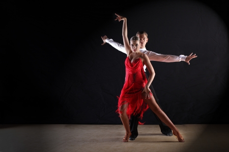 couple dancing: Latino dancers in ballroom against black