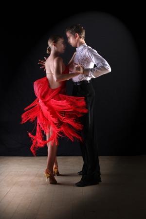 ballet dancing: Latino dancers in ballroom against on black Stock Photo