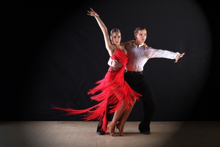 latin people: Latino dancers in ballroom against black background