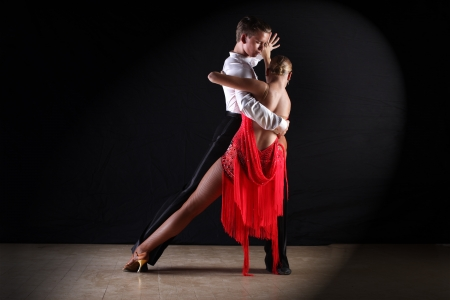 tango: Latino dancers in ballroom against on black Stock Photo