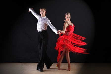 Latino dancers in ballroom against on black Stock Photo