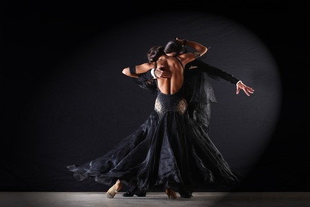 Latino dancers in ballroom against on black background photo