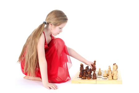 Cute girl 9 years old  play in chess on white photo