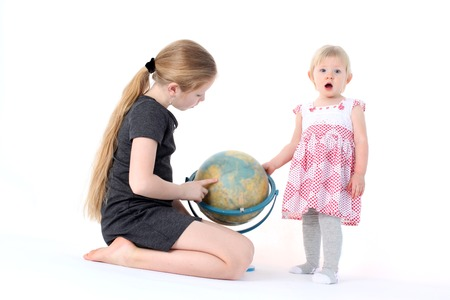 9 year old: adorable little two sisters 9 year and  1  year old with globe