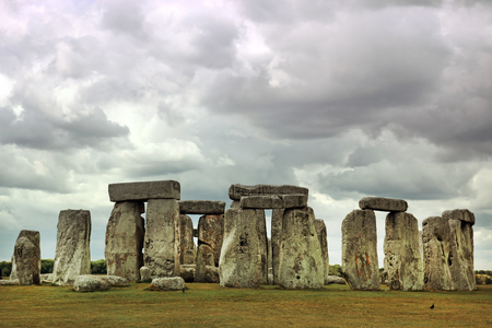 monolith: Stonehenge historic site under dramatic sky. Stonehenge is a UNESCO world heritage site in England with origins estimated at 3,000BC