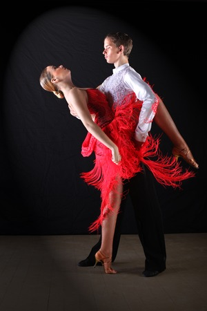 latino dancers in ballroom against black background Stock Photo