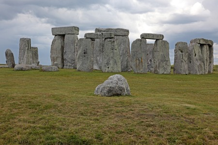 origins: Stonehenge historic site on green grass under blue sky. Stonehenge  site in England with origins estimated at 3,000BC Stock Photo