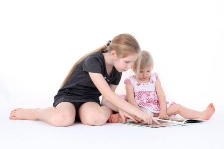 adorable little two sisters 9 year and  1  year old read book photo