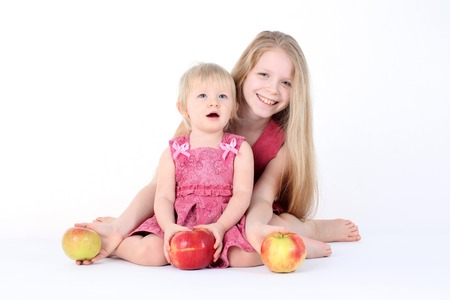 9 year old: adorable little two sisters 9 year and  1  year old with apple on white background Stock Photo