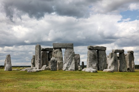 origins: Stonehenge historic site on green grass under blue sky. Stonehenge is a UNESCO world heritage site in England with origins estimated at 3,000BC