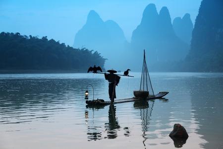 YANGSHUO - JUNE 18: Chinese man fishing with cormorants birds in Yangshuo, Guangxi region, traditional fishing use trained cormorants to fish, June 18, 2012 Yangshuo in Guangxi, China Editorial