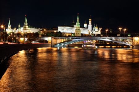 Moscow Kremlin Palace with Churches, Moskva river and Big Stone Bridge view through night rays of lamp, Russia
