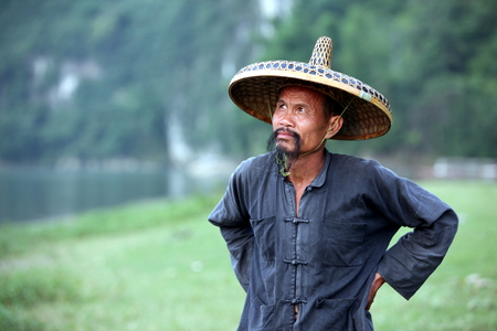 GUANGXI - JUNE 18: Chinese man in old hat in Guangxi region, traditional type of man face in China, June 18, 2012 in Guangxi, China. The average life expectancy among Chinese men is 72 years