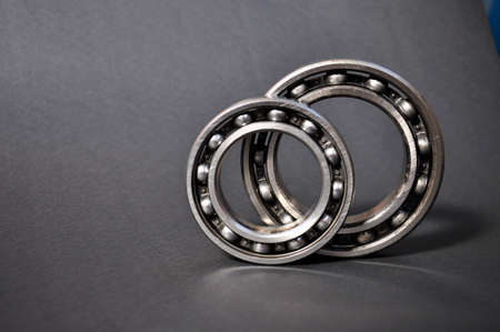 Two roller bearings on a gray background.