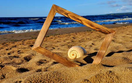Wooden photo frame and shell on the sand by the sea on a Sunny day Stock fotó