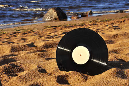 Vinyl record disk on the sand by the sea on a sunny day. Stock fotó