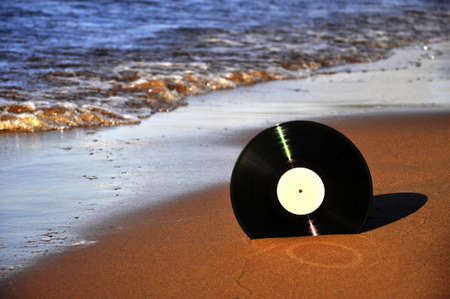 Vinyl record disk on the sand by the sea on a sunny day. 版權商用圖片 - 155892629
