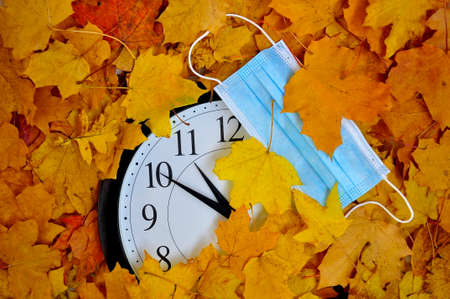 Wall clock and medical mask on the background of yellow autumn leaves.