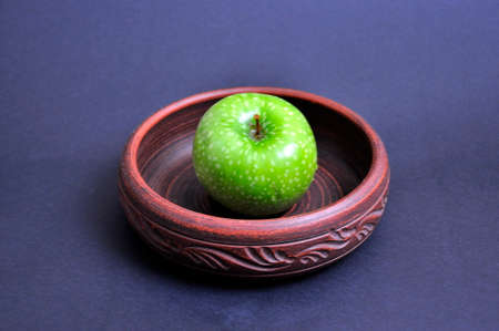 Green Apple in a round brown bowl on a dark background.