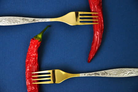 Two gold forks and two red chili peppers on a blue background.