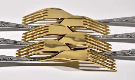 Gold forks stacked in a row on a gray background.