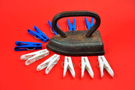 Old metal, vintage iron and multi-colored clothespins on a red background. Standard-Bild