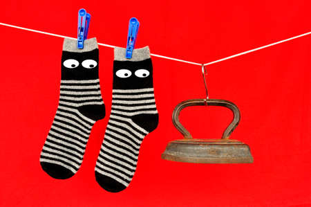 Socks hanging on a clothesline, fastened with clothespins and an old iron on a red background.