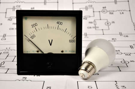 Energy-saving light bulb and vintage voltmeter. The concept of energy saving. Banque d'images