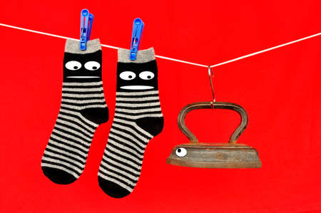 Striped socks hanging on a clothesline, fastened with clothespins and an old iron on a red background.