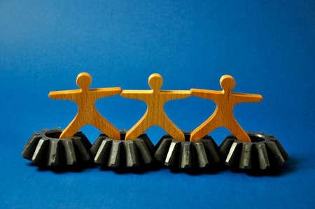 Metal cogs cogwheels and wooden figures of people holding hands.