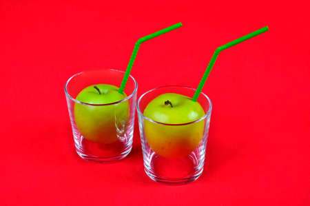 Apple juice in a glass with a drinking straw.