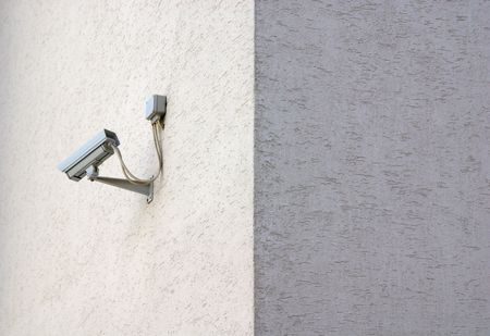 Security camera on sunlit building wall, no camera on wall in shadow photo