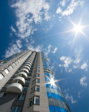 residental: Catch the sun. Tall office or residental building on blue sky with clouds. Wide-angle lens used.