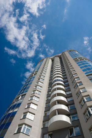 residental: Tall office or residental building on blue sky with clouds. Wide-angle lens used.