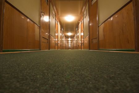 Wide-angle shot of long corridor with doors from floor level photo