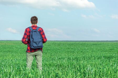 Man in the distance. He faces the field. On the back of the backpack. Sunny clear day. Stockfoto