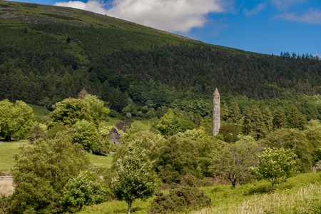 medeival: Round tower and ruins of church in Glendalough, Ireland Stock Photo